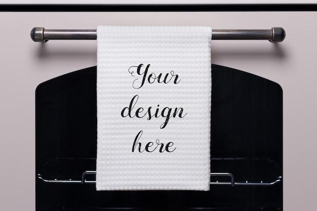 Witte keukenhanddoek hangt aan het handvat van de oven, mockup van het product.