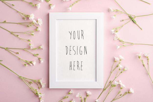 Witte lege fotolijst mockup met muis-oor vogelmuur bloemen op roze achtergrond, bovenaanzicht kopie ruimte