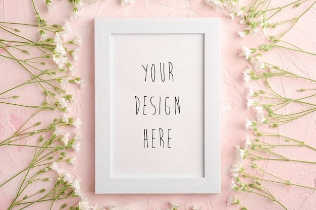 Witte lege fotolijst mockup met muis-oor vogelmuur bloemen op roze gestructureerde achtergrond, bovenaanzicht kopie ruimte