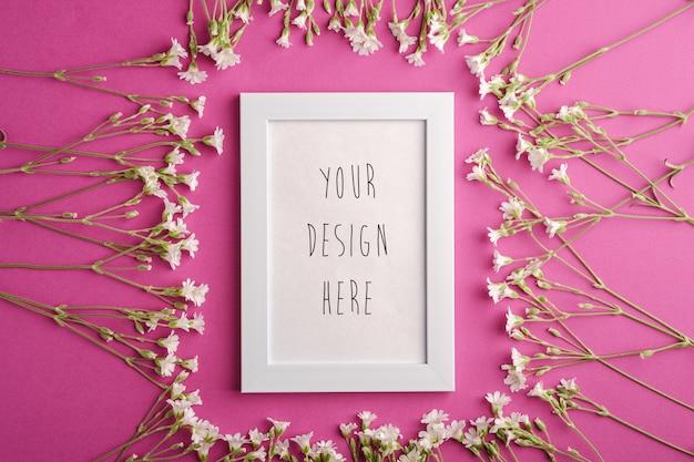 Witte lege fotolijst mockup met muis-oor vogelmuur bloemen op roze paars, bovenaanzicht