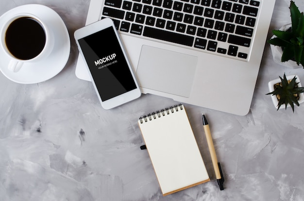 Witte smartphone met zwart leeg scherm op bureau met laptop en kopje koffie