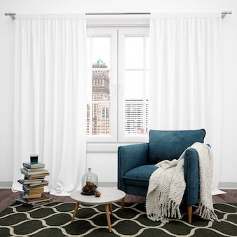 Woonkamer met elegante fauteuil en groot raam, boeken op de vloer gestapeld