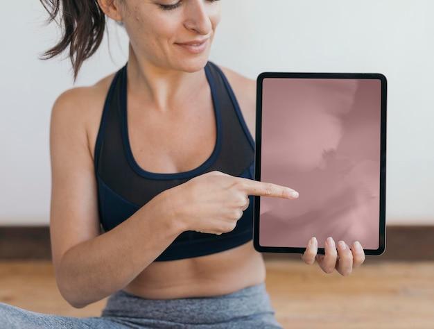Yoga-instructeur die een mobiel telefoonbehang van een digitaal tabletmodel toont