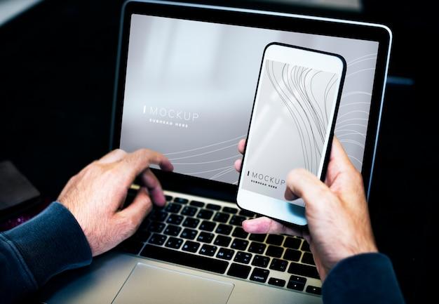 Zakenman die laptop en een mobiel telefoonmodel met behulp van