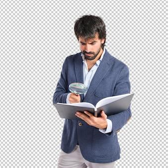 Zakenman die met loupe een boek over witte achtergrond reding