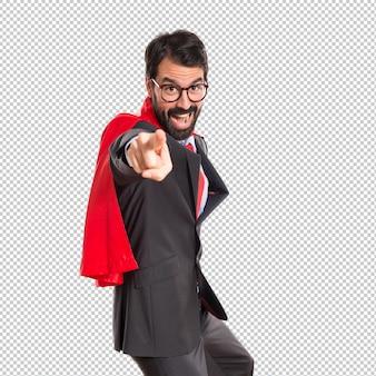 Zakenman gekleed als superheld wijzend naar de voorkant