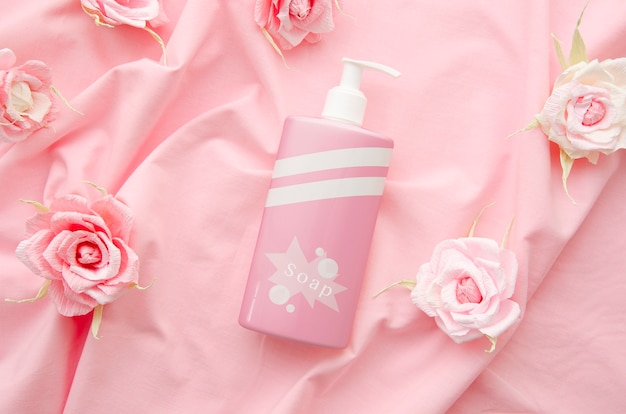Zeepfles op roze stoffenachtergrond
