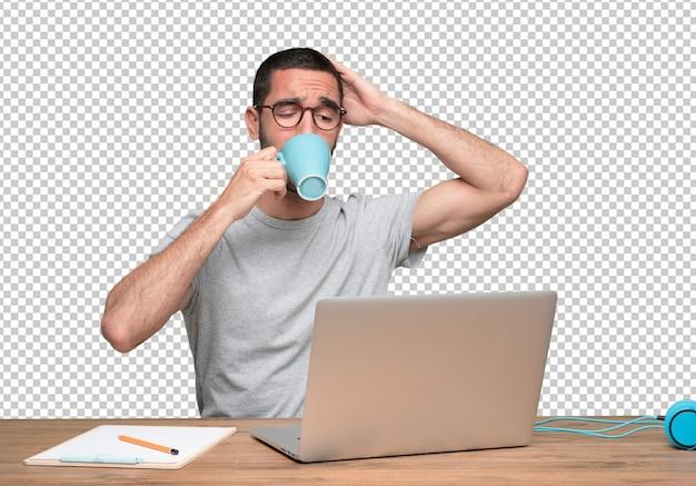 Zekere jonge man zit aan zijn bureau koffie drinken