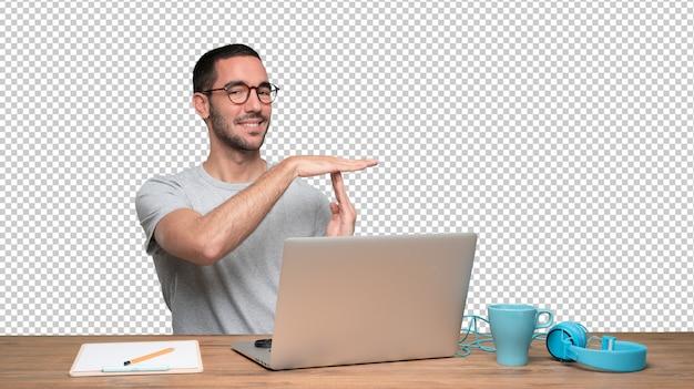 Zekere jonge man zit aan zijn bureau met een gebaar van pauze