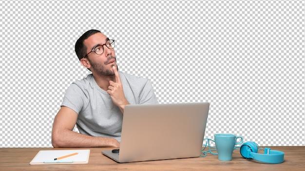 Zekere jonge mens met een gebaar van twijfel die bij zijn bureau zitten