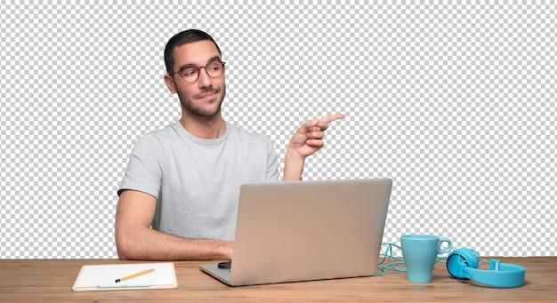 Zekere jonge mensenzitting bij zijn bureau en het richten met zijn hand