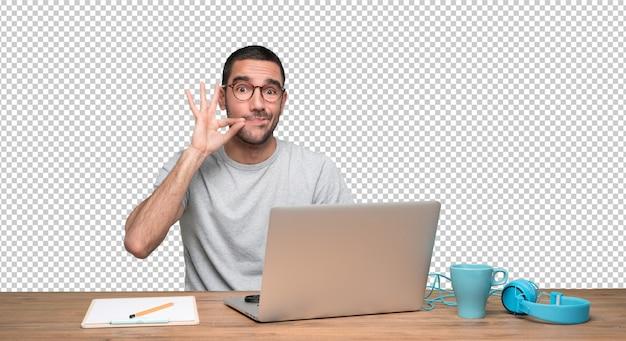 Zekere jonge mensenzitting bij zijn bureau met een gebaar van het houden van een geheim