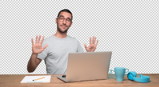 Zekere jonge mensenzitting bij zijn bureau met een levensonderhoud kalm gebaar