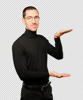 Zelfverzekerde jonge man die een gebaar doet om iets met zijn handen vast te houden