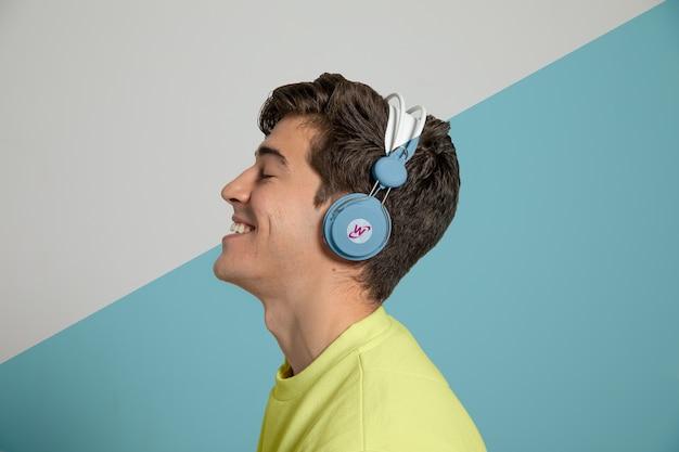 Zijaanzicht van de mens die van muziek op hoofdtelefoons geniet