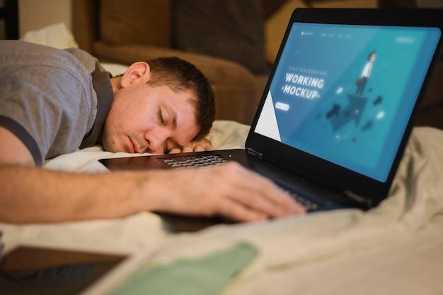Zijaanzicht van de mens in slaap vallen tijdens het werken op laptop