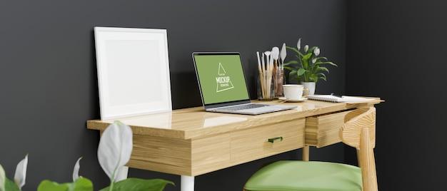 Zijaanzicht van de werkruimte van de kunstenaar met laptop-verfgereedschappen en decoraties in de loft-kantoorruimte aan huis