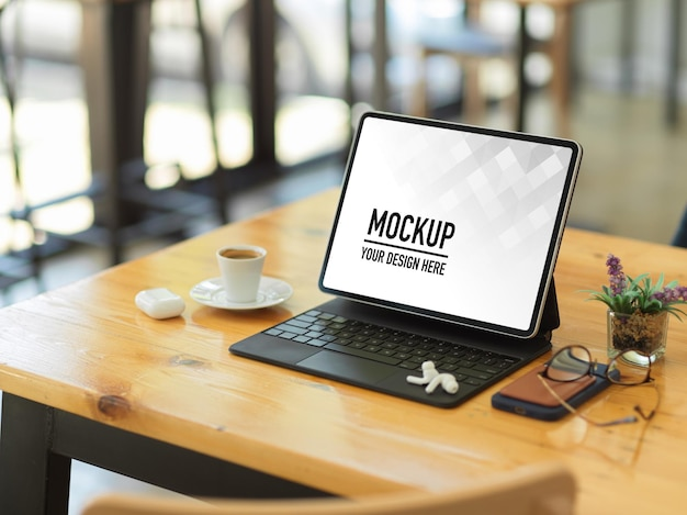 Zijaanzicht van digitale tablet, accessoires en koffiekopje op houten tafel