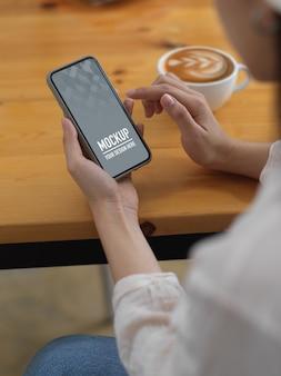 Zijaanzicht van het model van de vrouwelijke holdingssmartphone