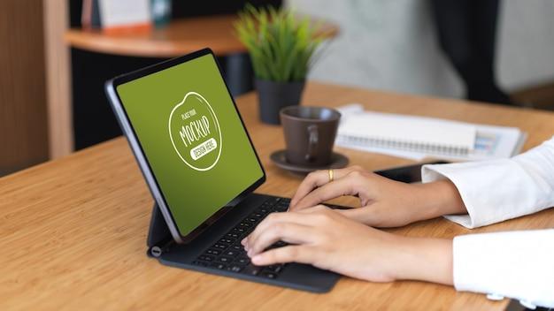 Zijaanzicht van vrouwelijke hand typen op tablettoetsenbord op houten tafel met koffiekopje en benodigdheden