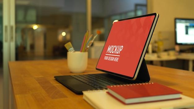 Zijaanzicht van werktafel met digitale tablet, penselen en notitieboekjes