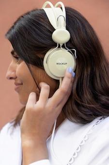 Zijaanzichtvrouw die naar muziek luistert via een koptelefoon