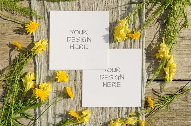 Zomer briefpapier mockup wenskaart of bruiloft uitnodiging met gele bloemen op een oud hout
