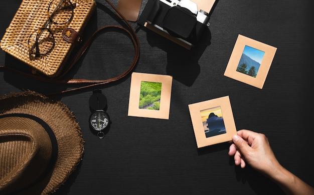Zomer reizen van reiziger accessoires set. pick-up fotolijst met de hand op zwarte houten tafel