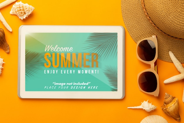 Zomer samenstelling met tablet mockup en strand accessoires op oranje oppervlak