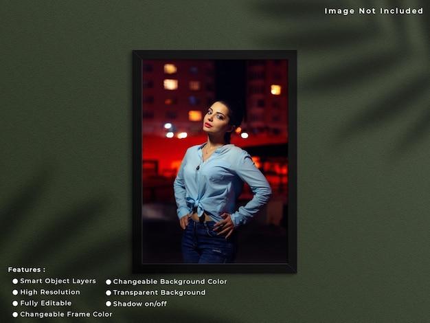 Zwart verticaal fotolijstmodel dat op muurachtergrond hangt met schaduw.