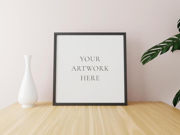Zwart vierkant framemodel op houten tafel met vaas en planten. 3d-rendering.