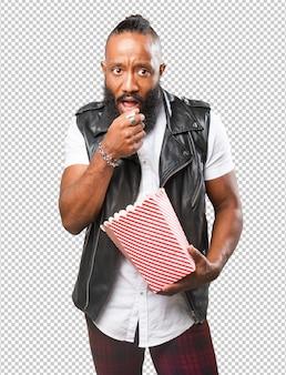 Zwarte man die popcorn eet