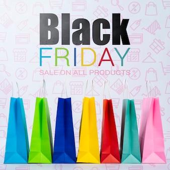 Zwarte vrijdag banner met kleurrijke papieren zakken