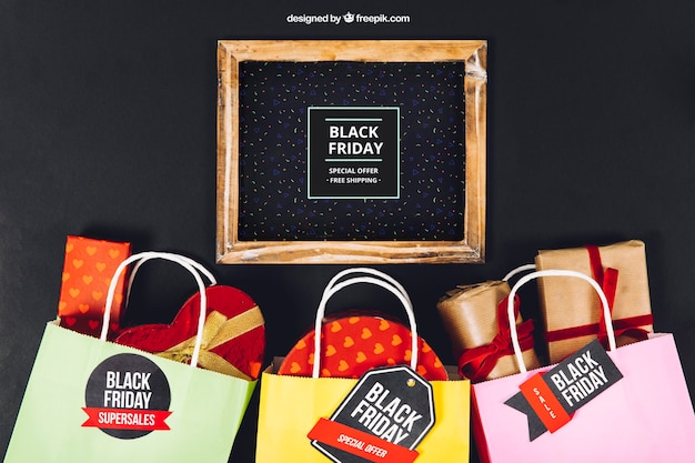Zwarte vrijdag mockup met leisteen en tassen vol cadeaus