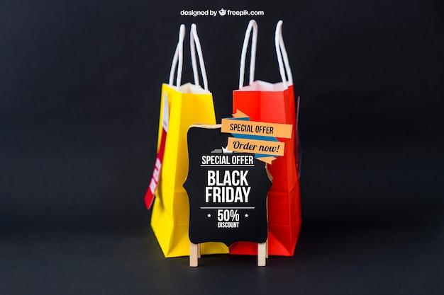 Zwarte vrijdag mockup met twee zakken achter het bord