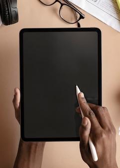 Zwarte vrouw die een digitaal tabletmodel gebruikt