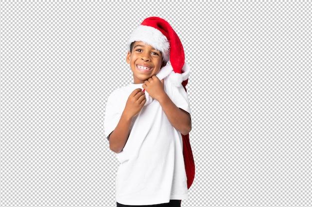 Afro-américain garçon avec un chapeau de noël et prenant un sac avec des cadeaux