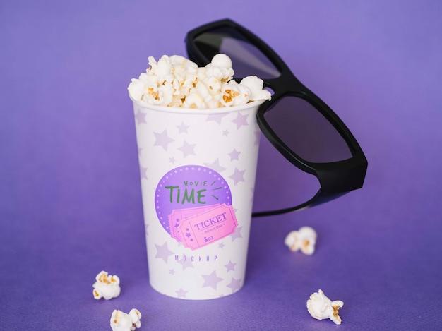 Angle élevé de tasse avec pop-corn et lunettes de cinéma