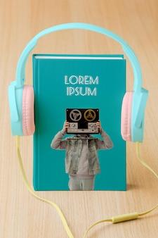 Arrangement avec maquette de couverture de livre et écouteurs