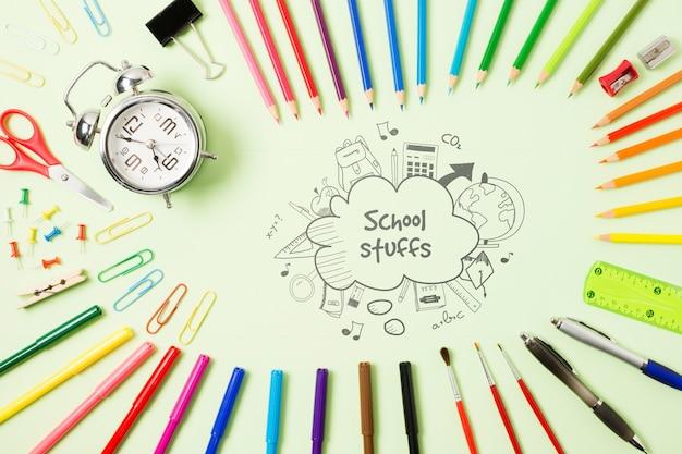 Arrangement de vue de dessus avec des crayons et une horloge