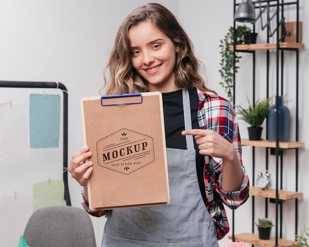Artiste féminine smiley tenant le bloc-notes maquette et pointant vers elle