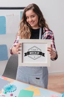 Artiste féminine de smiley tenant un cadre de maquette