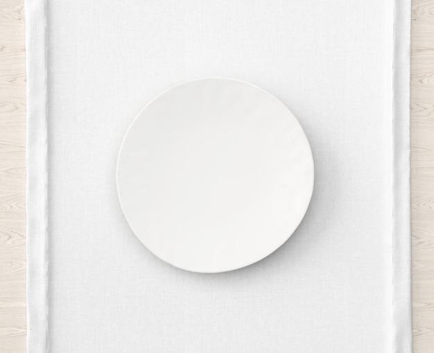Assiette blanche sur nappe