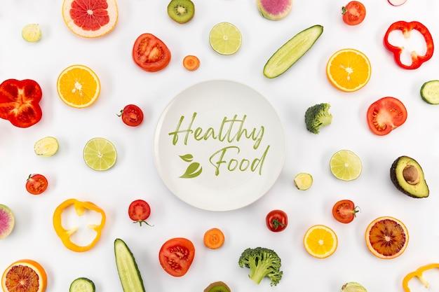 Assiette entourée de légumes et vue de dessus de fruits