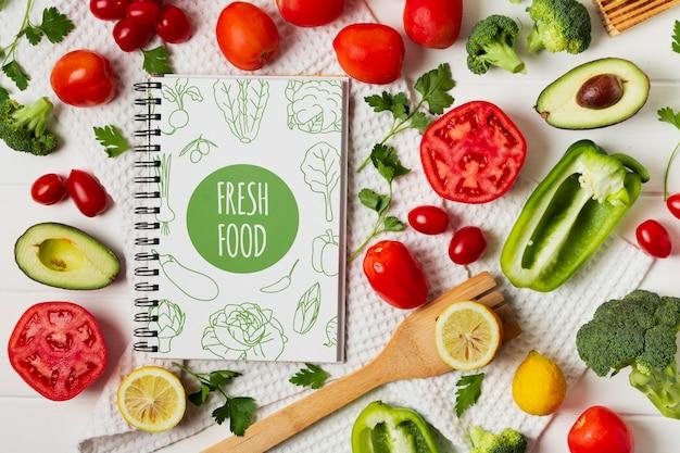 Assortiment de légumes vue de dessus avec maquette de cahier