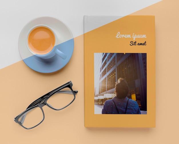 Assortiment de maquette de couverture de livre avec tasse de café et verres