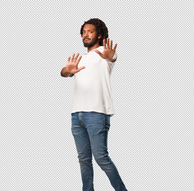 Beau afro-américain sérieux et déterminé, mettre la main devant, arrêter le geste, nier