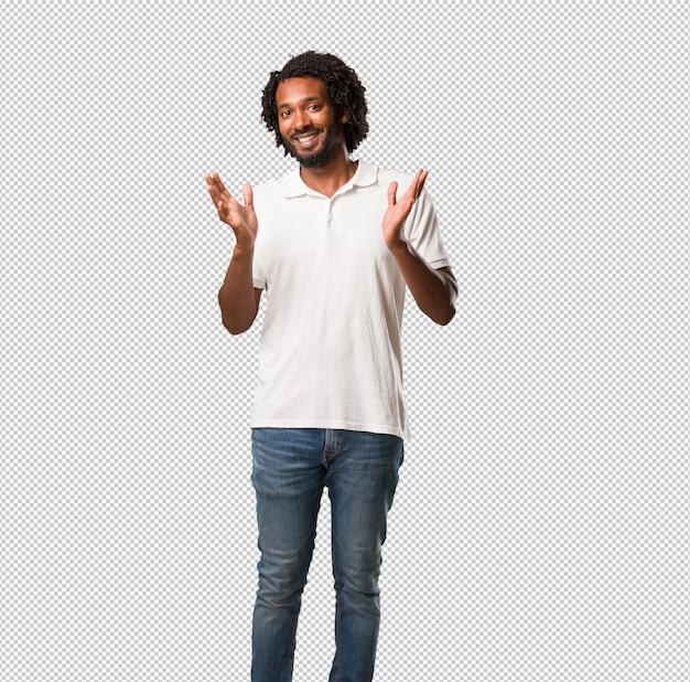 Beau afro-américain surpris et choqué, regardant avec des yeux grands ouverts, excité par une offre ou par un nouvel emploi, gagne