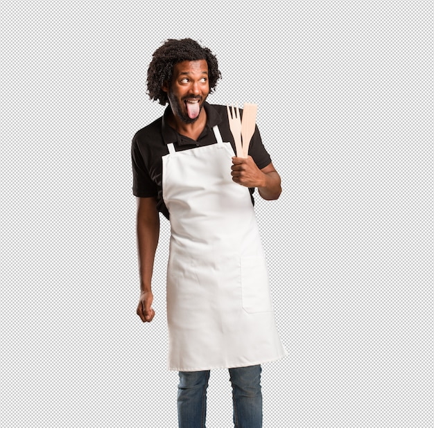 Beau boulanger afro-américain expression de confiance et d'émotion, amusant et amical, montrant la langue comme signe de jeu ou de plaisir