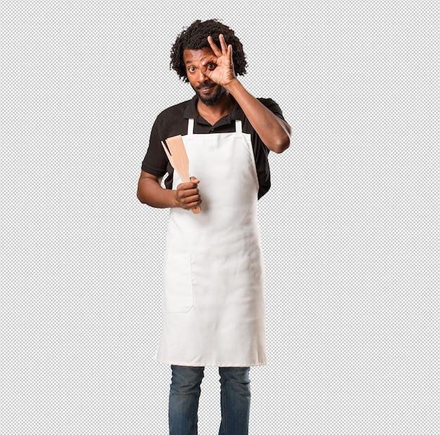 Beau boulanger afro-américain gai et confiant faisant un geste ok, excité et hurlant, concept d'approbation et de succès